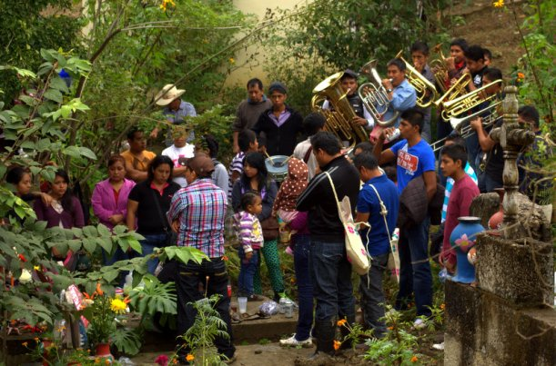 A brass band serenades a mourning family at the graveyard on Day of the Dead
