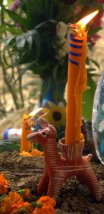 Clay donkey candle-holder standing on a grave on Day of the Dead